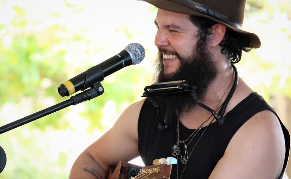 One man band Murilo Augustus canta e toca simultaneamente violão, gaita, cajon, kazoo e pandeiro de pé