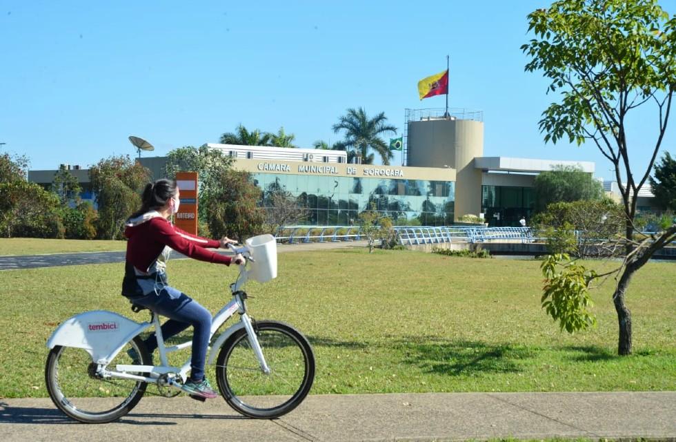 Mulher pedala em bicicleta do integrabike no Paço Municipal, em frente à Câmara de Sorocaba.